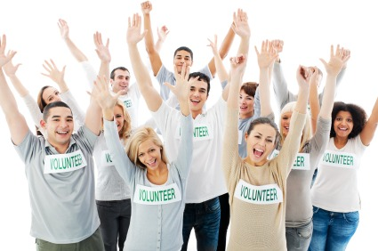 Group of cheerful volunteers with their hands up.